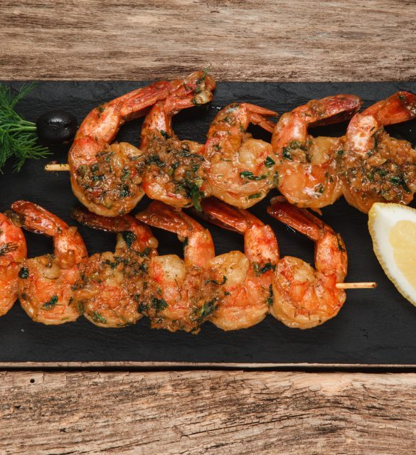 Japanese cuisine. Fried shrimps served on black slate with herbs and lemon, top view. Restaurant menu photo.