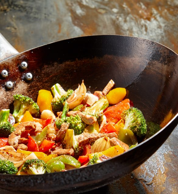 Tasty vegetable dish with broccoli and colorful peppers cooked in oil stained asian wok recipe against a rustic background