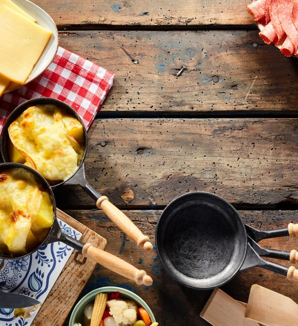 Traditional regional Swiss cuisine with melted raclette cheese over boiled potatoes served with cold meats, rustic border of the ingredients and skillets with copy space