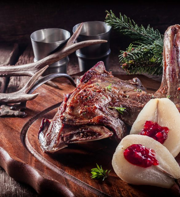 Roasted Vension Haunch Served on Wooden Tray with Prepared Pears Accented by Evergreen Sprigs and Deer Antlers