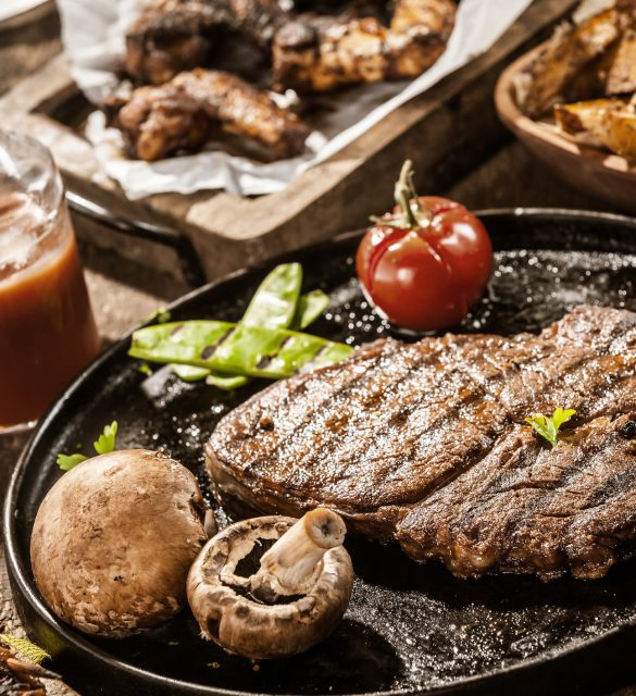 Rustic country meal of grilled ribe eye beef steak with mushrooms and tomato served with homemade ketchup and assorted barbecued meats on a summer picnic