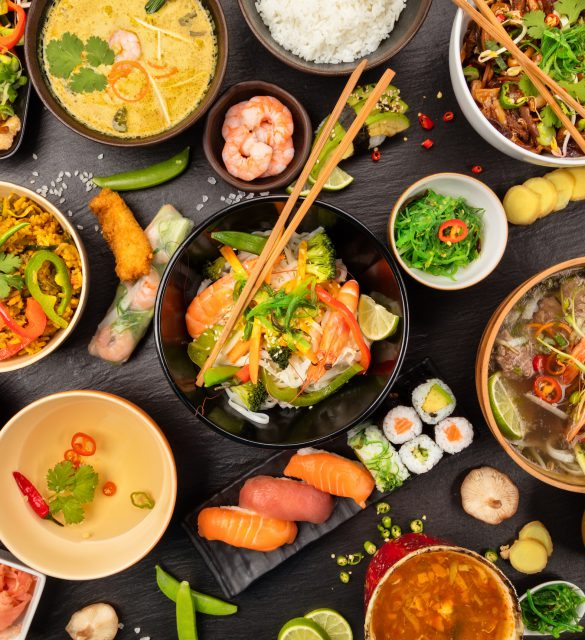Asian food table with various kind of chinese food, noodles, chicken, pork, beef, sour soup, rice, spring rolls, sushi, prawns and many others. Served on black stone table, top view.